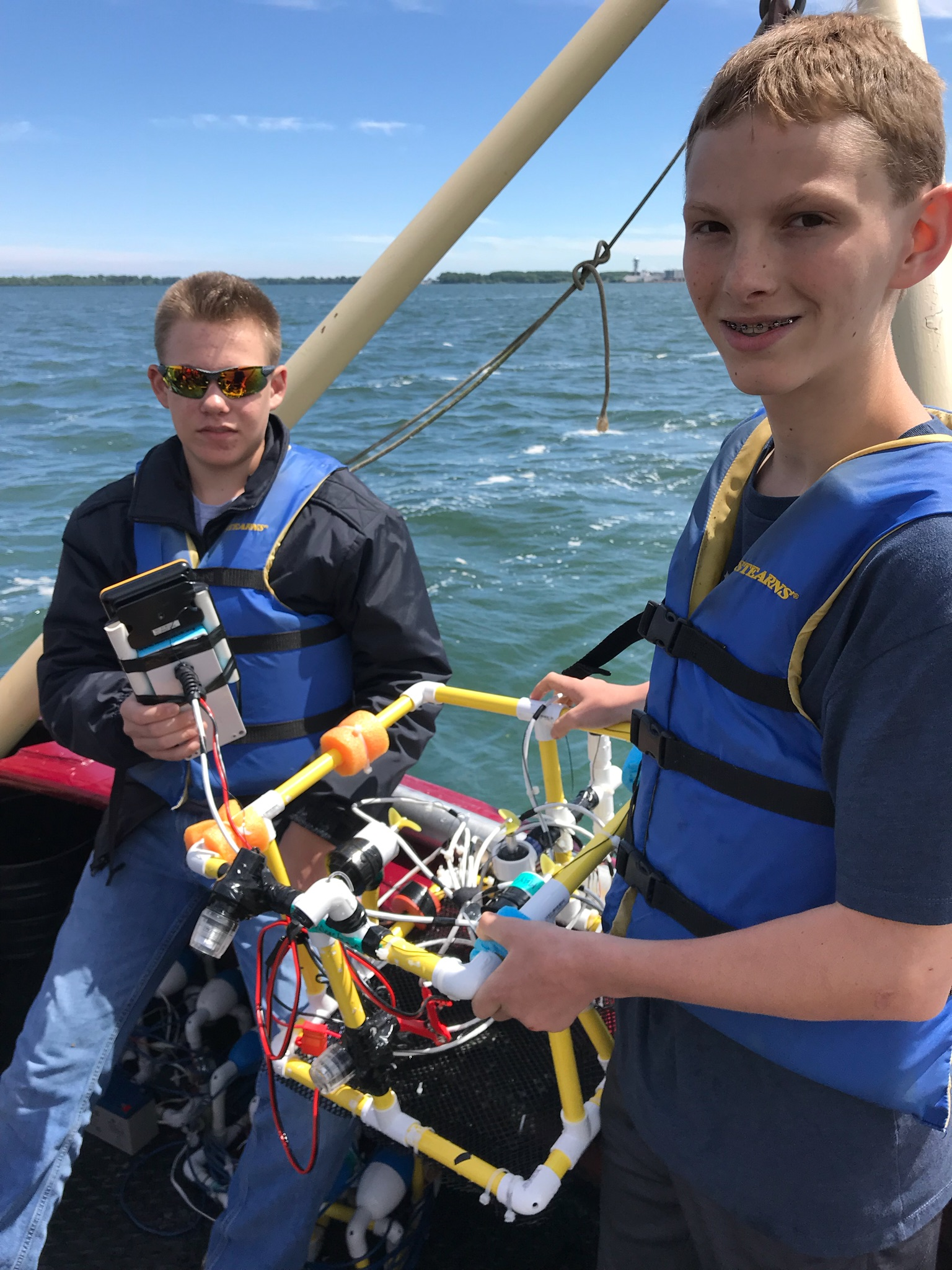 students aboard research vessel on lake erie testing out submersible robot
