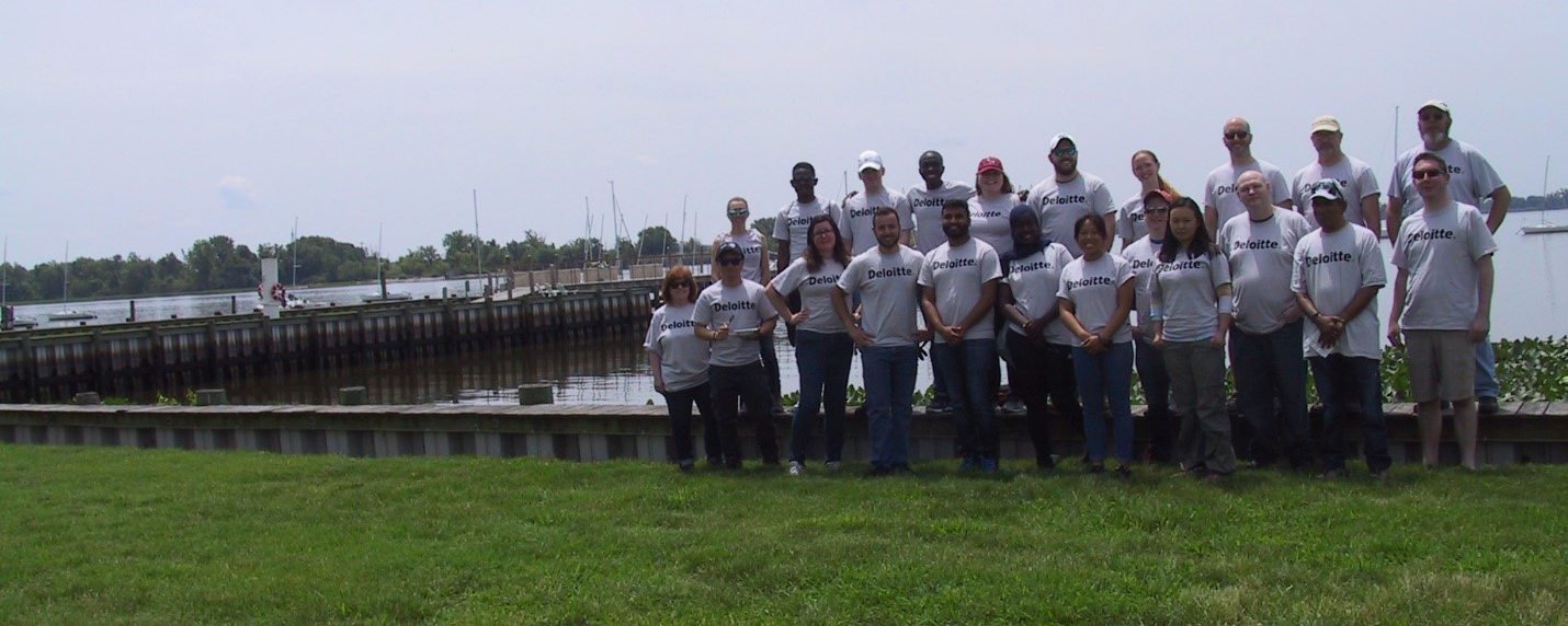 Volunteer from Deloitte offices throughout the Delaware Valley pose along the Corinthian Yacht Club waterfront with Little Tinicum Island showing in the background.