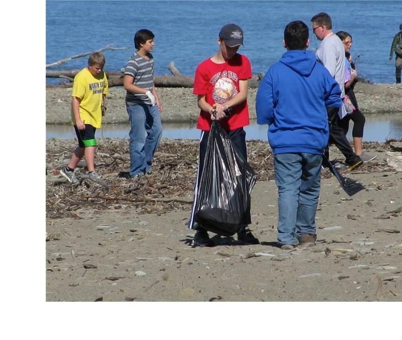 students clean up trash along shoreline