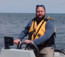 Research Director Sean Rafferty steers a boat on Lake in Erie in PA