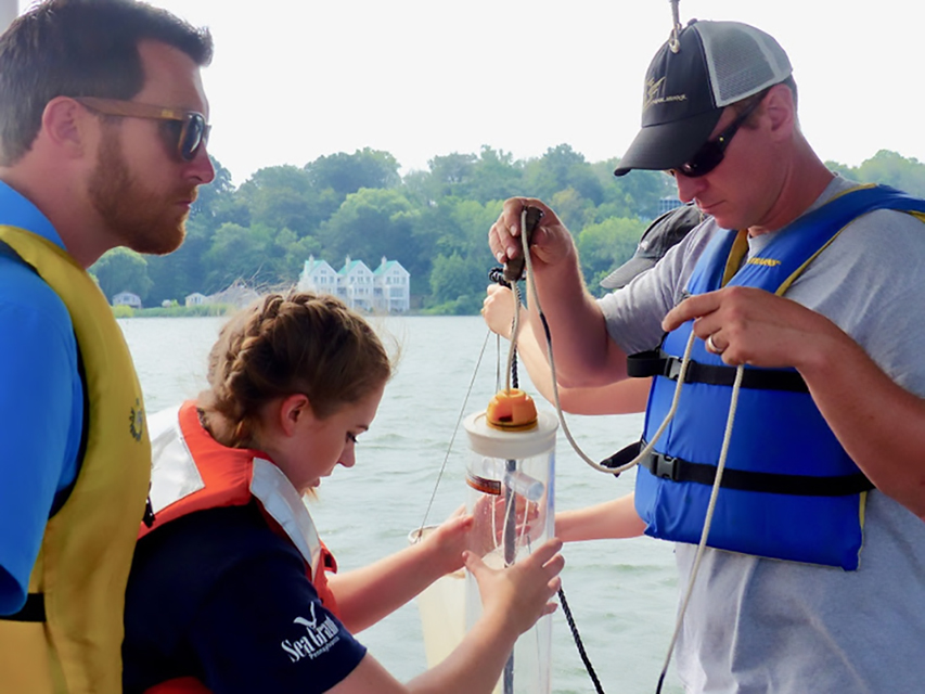 teachers and shipboard science program educator look at water sample
