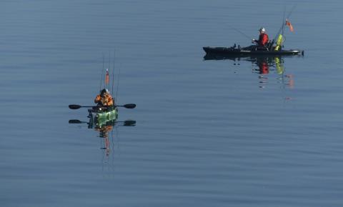 photo of two men in kayaks fishing